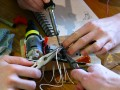 three students soldering an arduino board